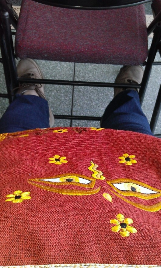 feet resting on back frame of chair, buddha eyes of compassion bag