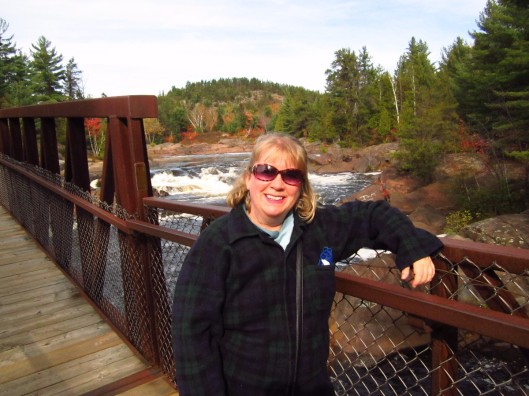 Blonde woman at the bridge over Onaping River and Falls